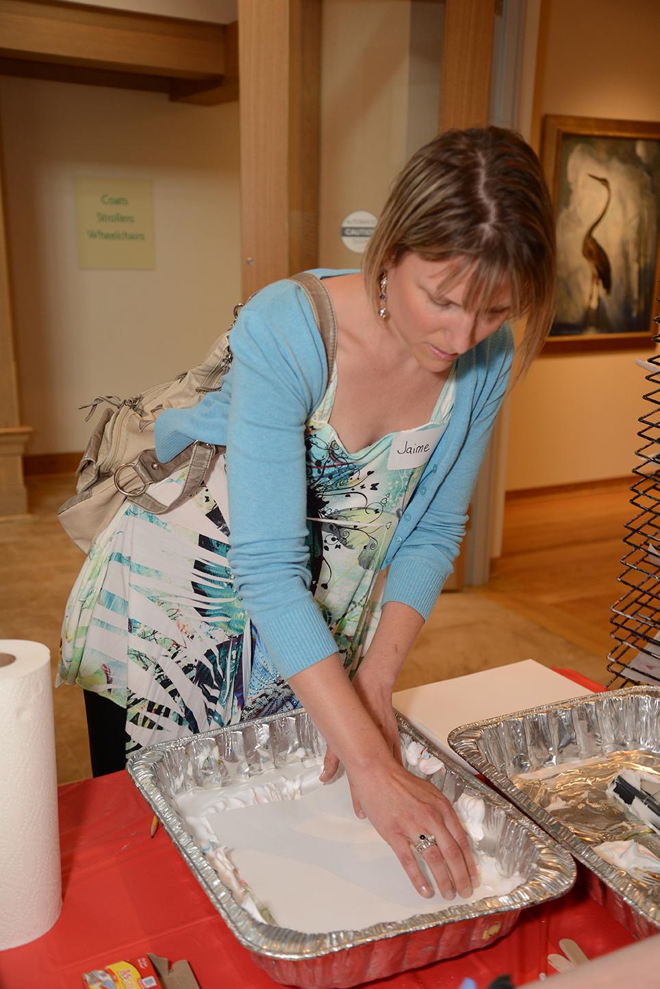 woman pressing cardstock onto swirled foam