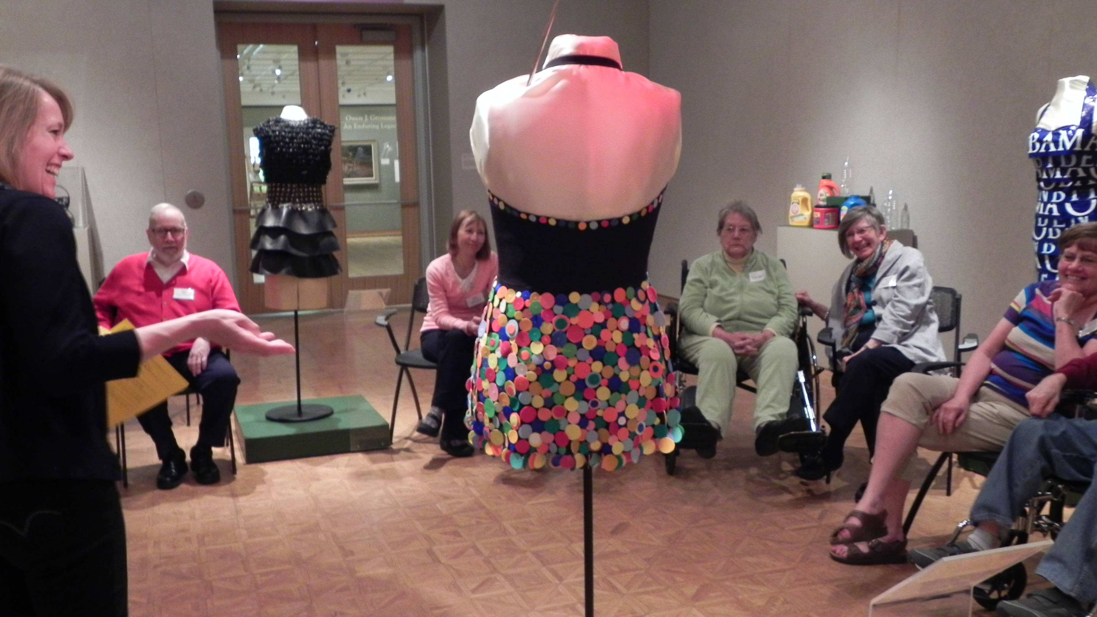 SPARK! participants gather amid upcycled fashions in a Woodson Art Museum gallery.