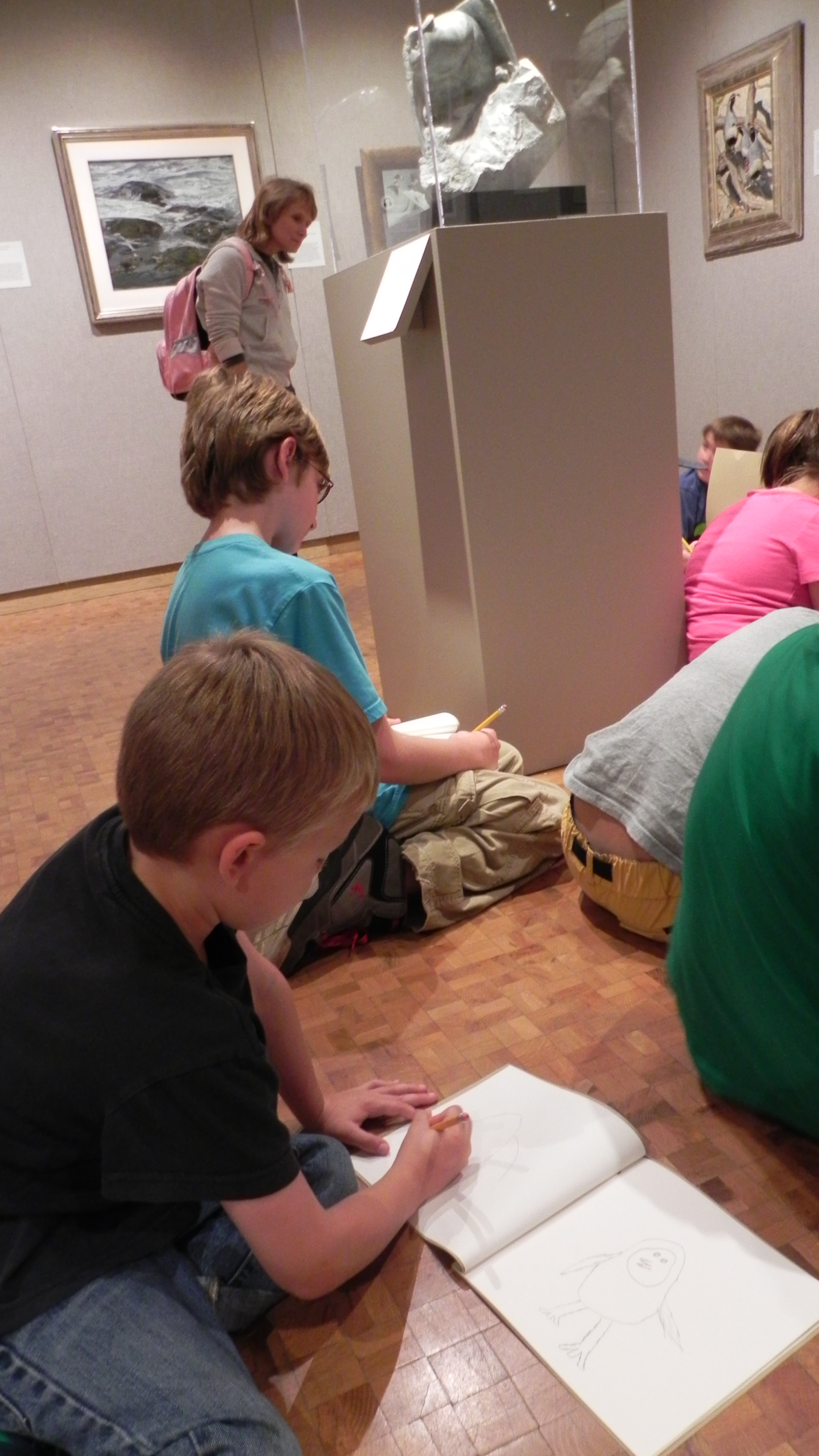 Children draw in sketchbooks in the galleries.
